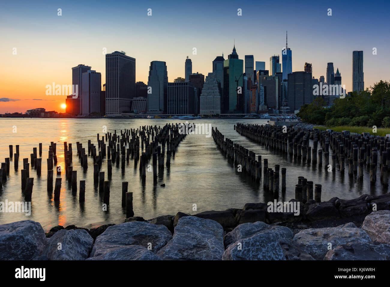 Wolkenkratzer von Manhattan und Holz-pilings bei Sonnenuntergang von Brooklyn Bridge Park. Manhattan, New York City Stockbild