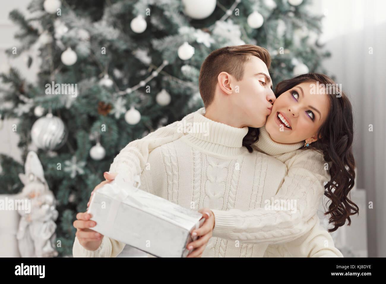 Paar Teenager zu Weihnachten. Sie umarmt ihren Freund und hält ein ...