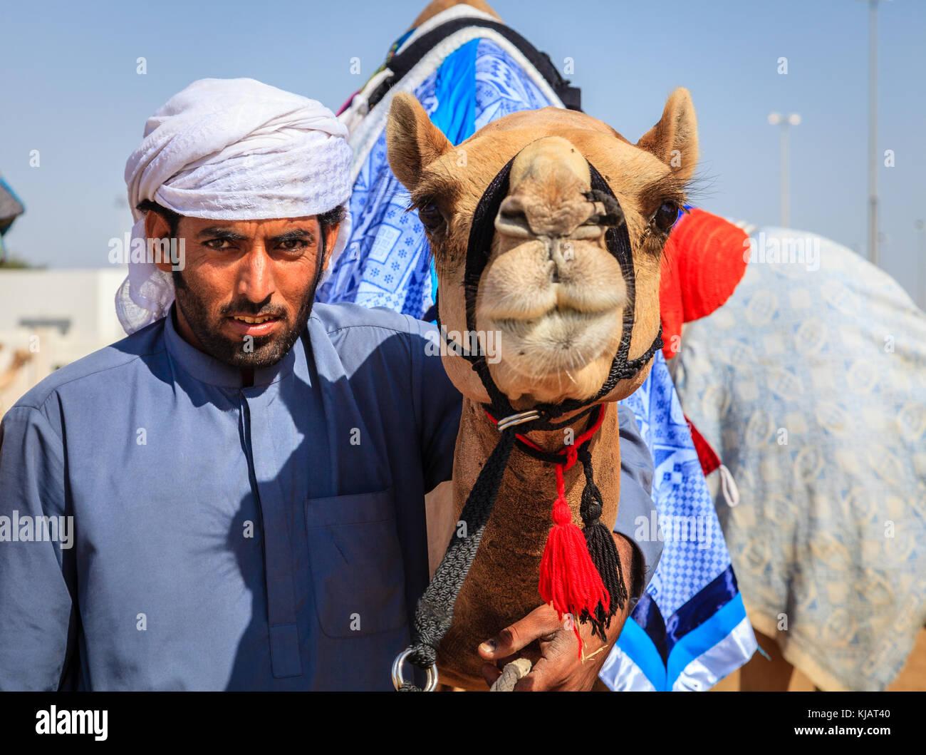 Dubai, Vereinigte Arabische Emirate - 25. März 2016: camel Handler mit seinem Tier in Dubai camel Racing Club Stockfoto