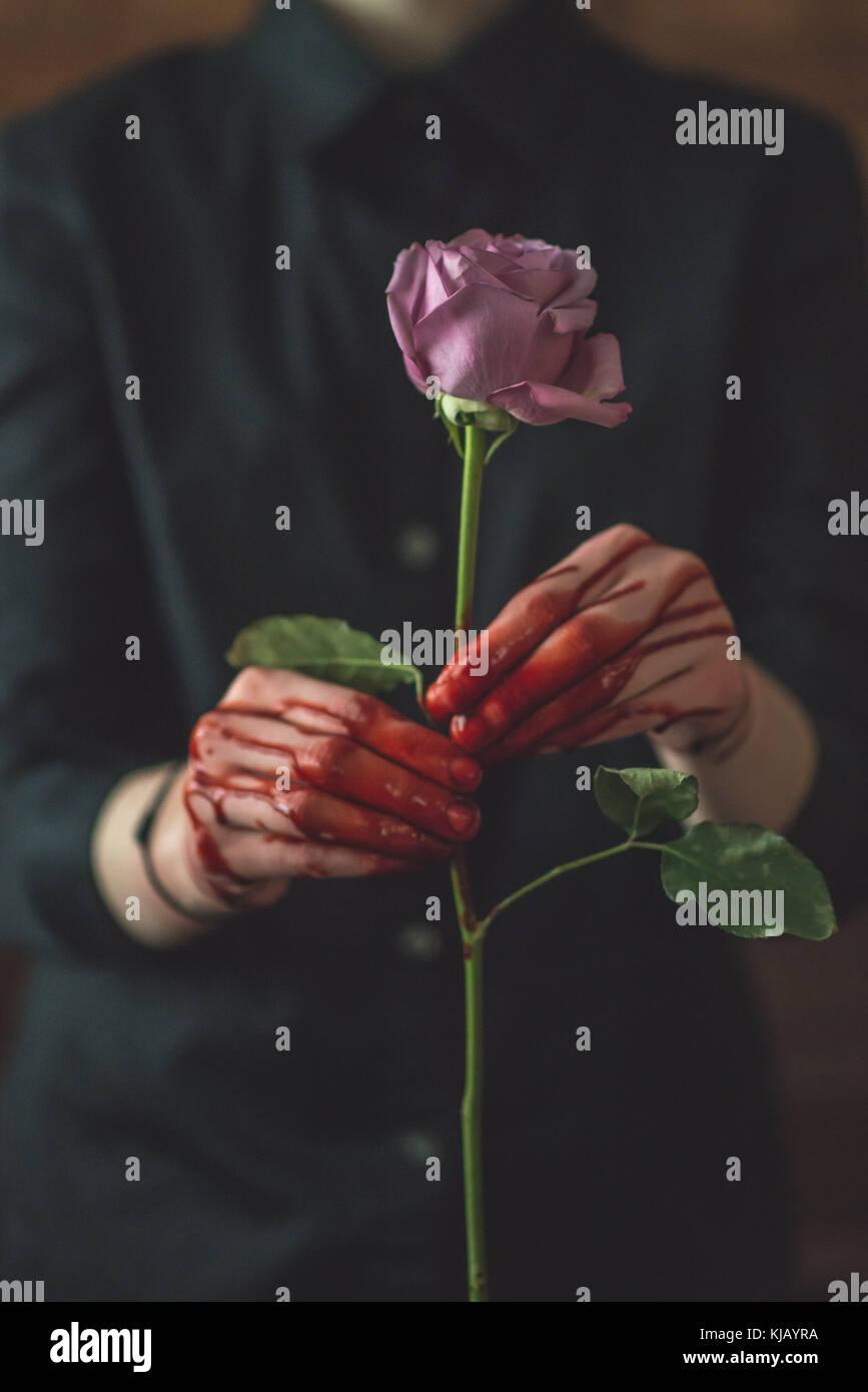Junge Frauen, die sich in einem blutigen Rose Stockbild