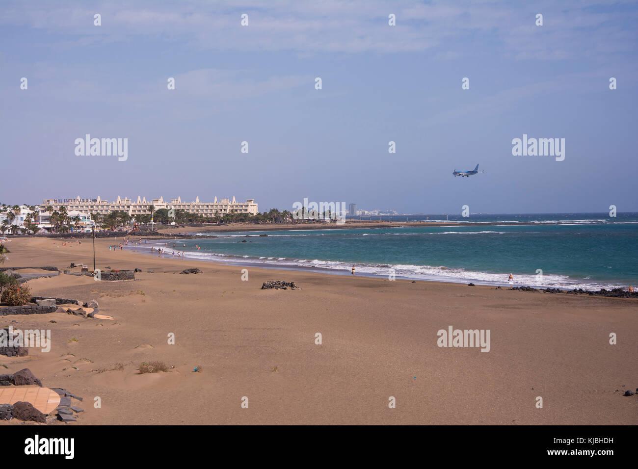 Strand Los Pocillos mit einem Flugzeug an am Flughafen Arrecife Stockbild