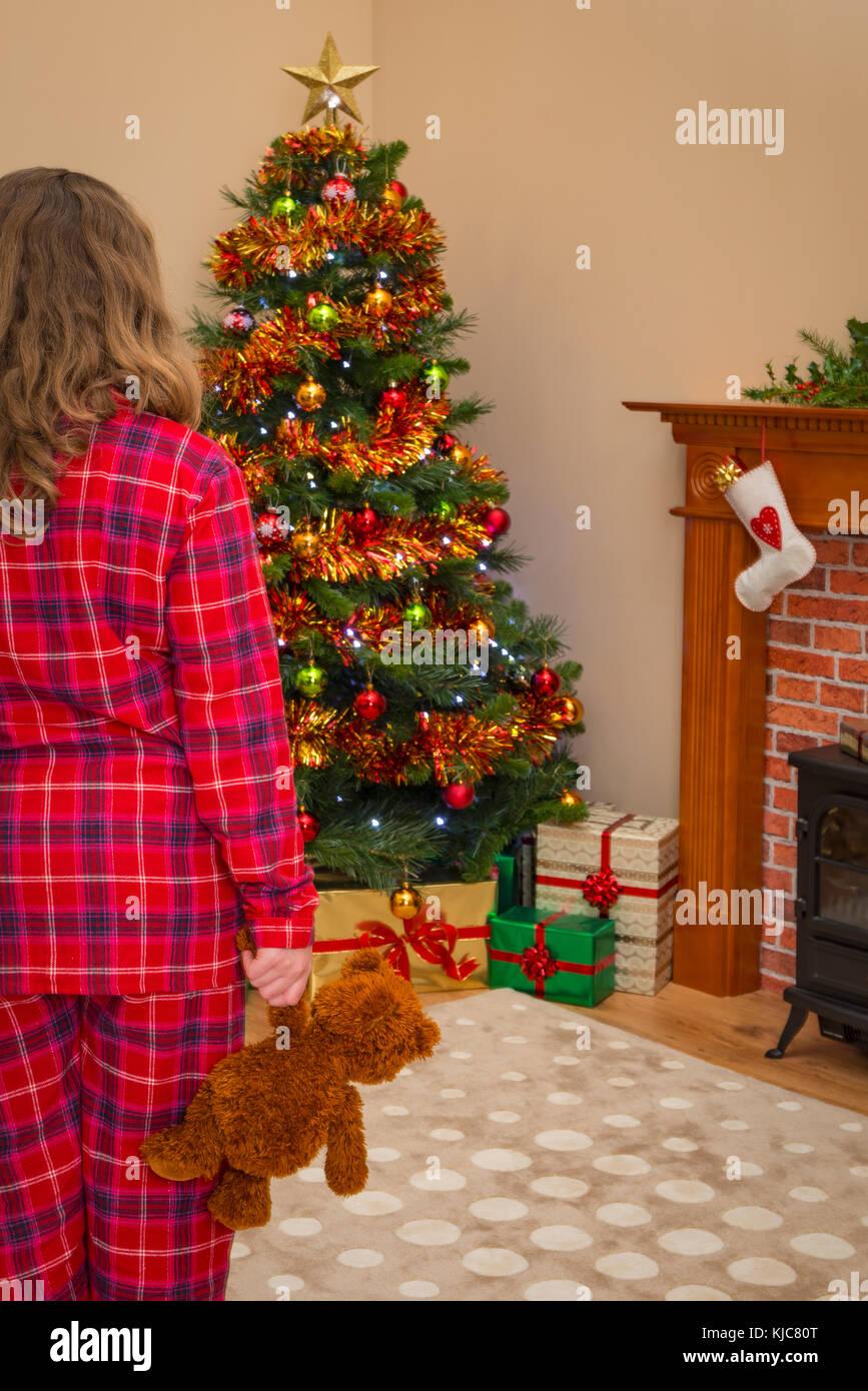 Ein junges Mädchen hält ein Teddybär auf Weihnachten Morgen, als Sie ...
