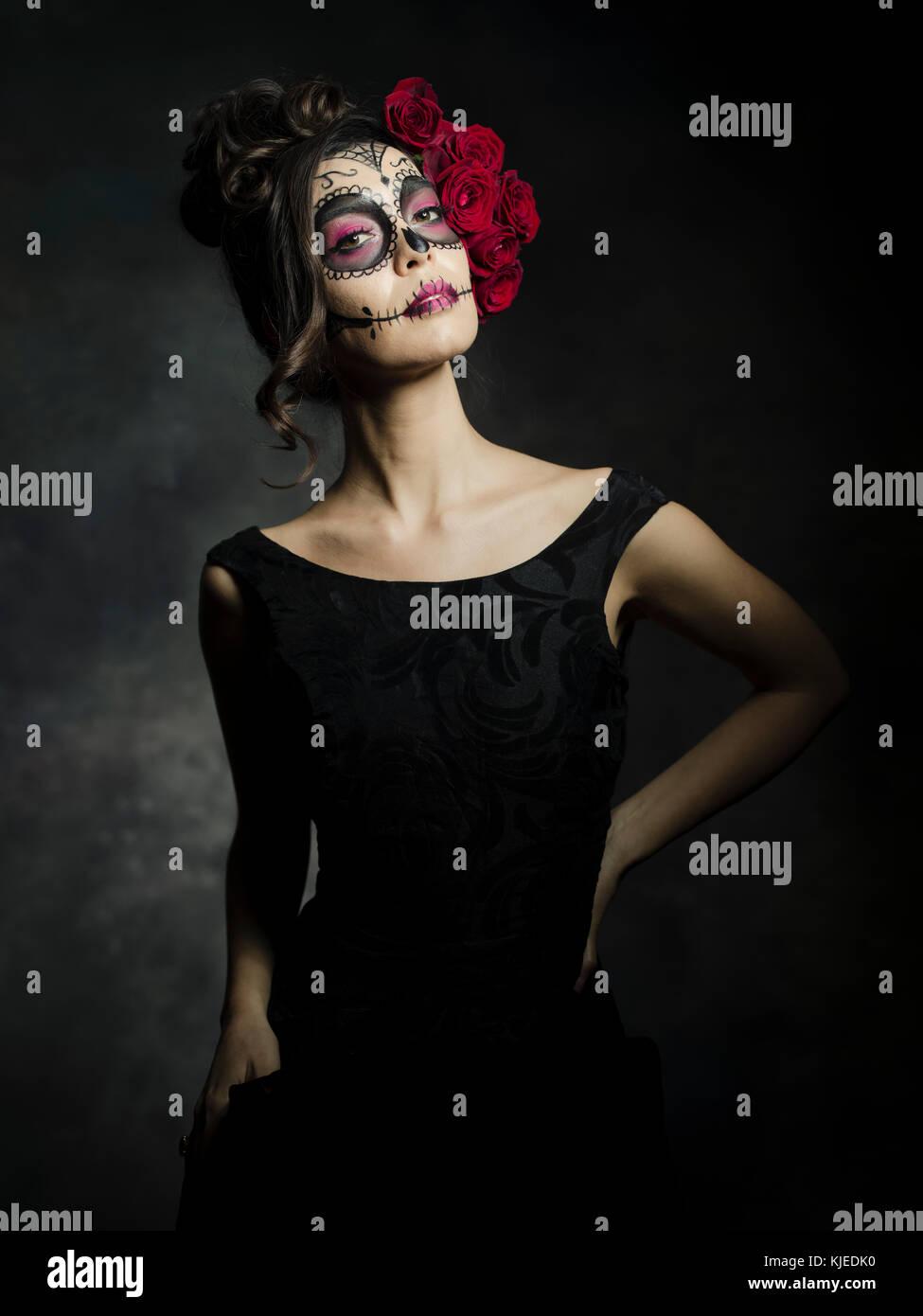 Schöne mexikanische amerikanische Frau feiern Día de los Muertos (Día de Muertos) ist der mexikanische Feiertag auch als Tag der Toten mit dem Schädel Make-up und Rosen im Stil von Catrina bekannt. Stockfoto