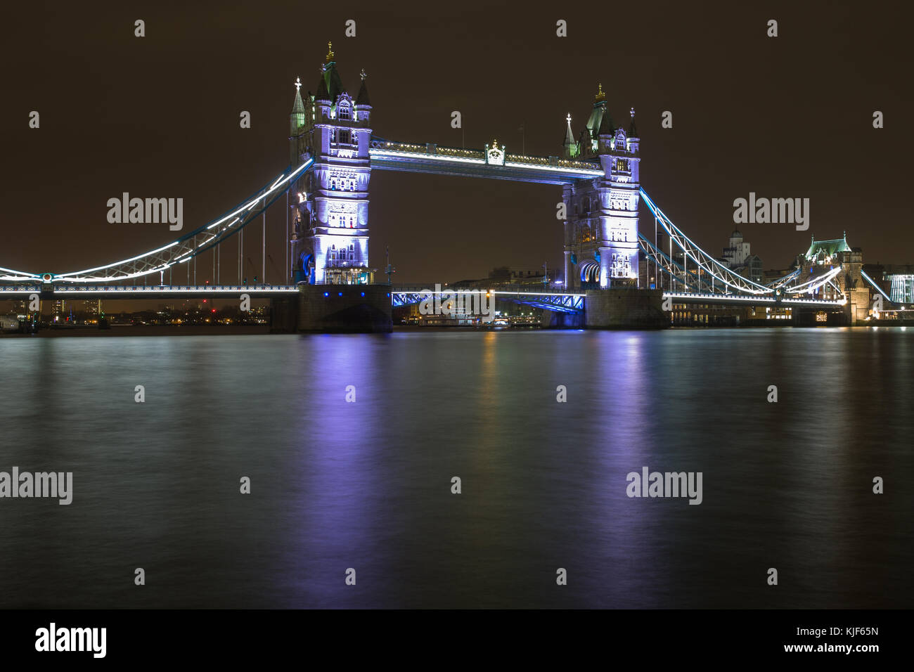 Die Tower Bridge über die Themse in der Nacht beleuchtet in Lila mit Reflexion im Wasser - London, Großbritannien Stockbild