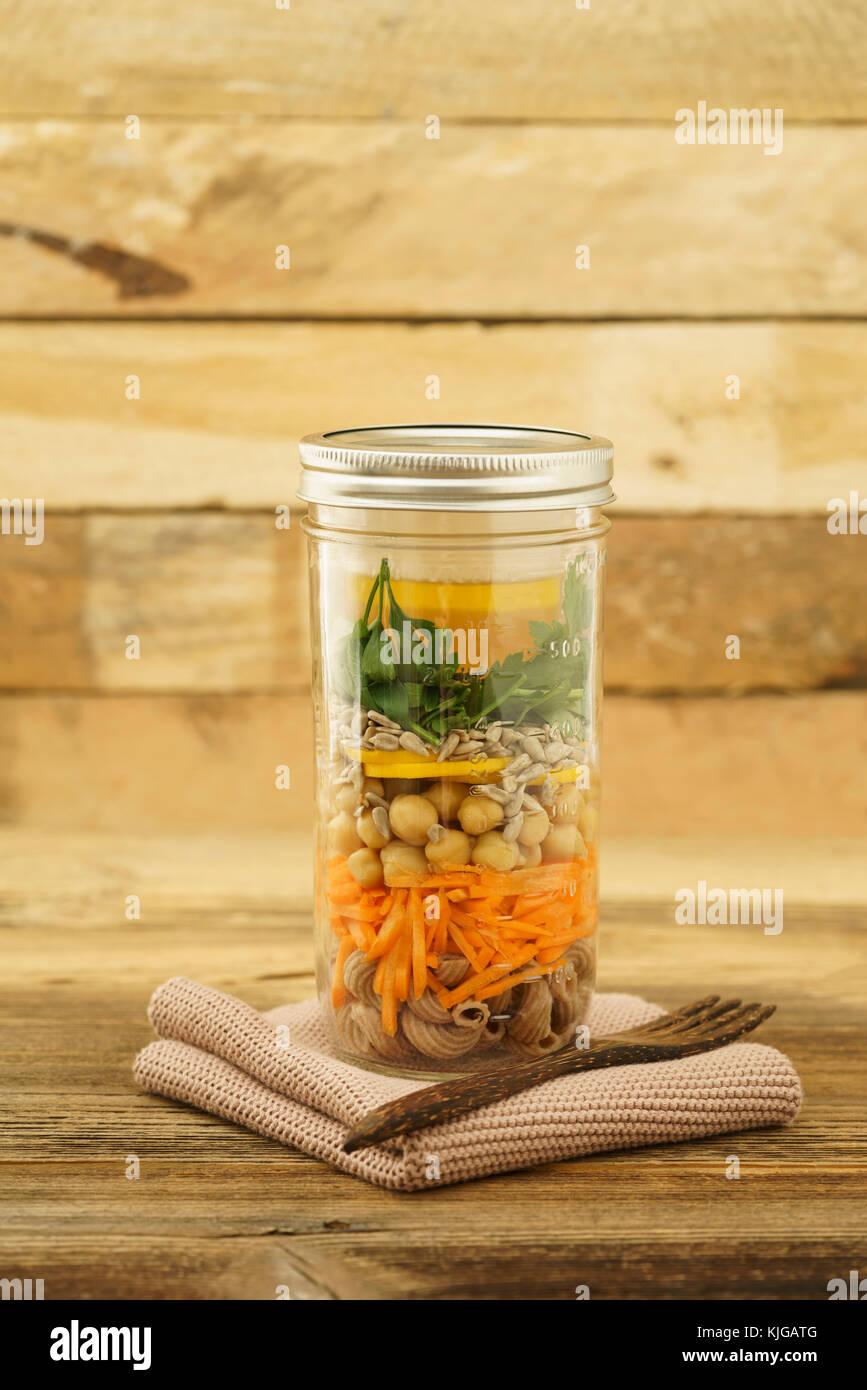 Veganer und vegetarischer Salat zum Mitnehmen im Glas mit Vollkornnudeln, gestifteten Möhren, Kichererbsen, gelben Stockfoto