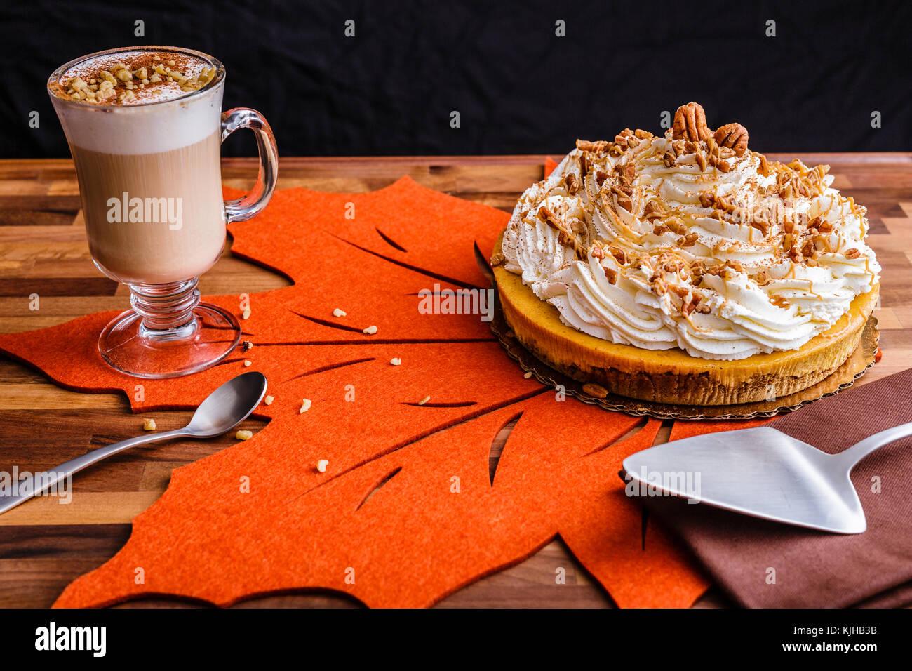 Genießen Thanksgiving mit einem Kürbis kuchen Käsekuchen und eine Tasse Milchkaffee Kaffee. Einstellung Stockbild