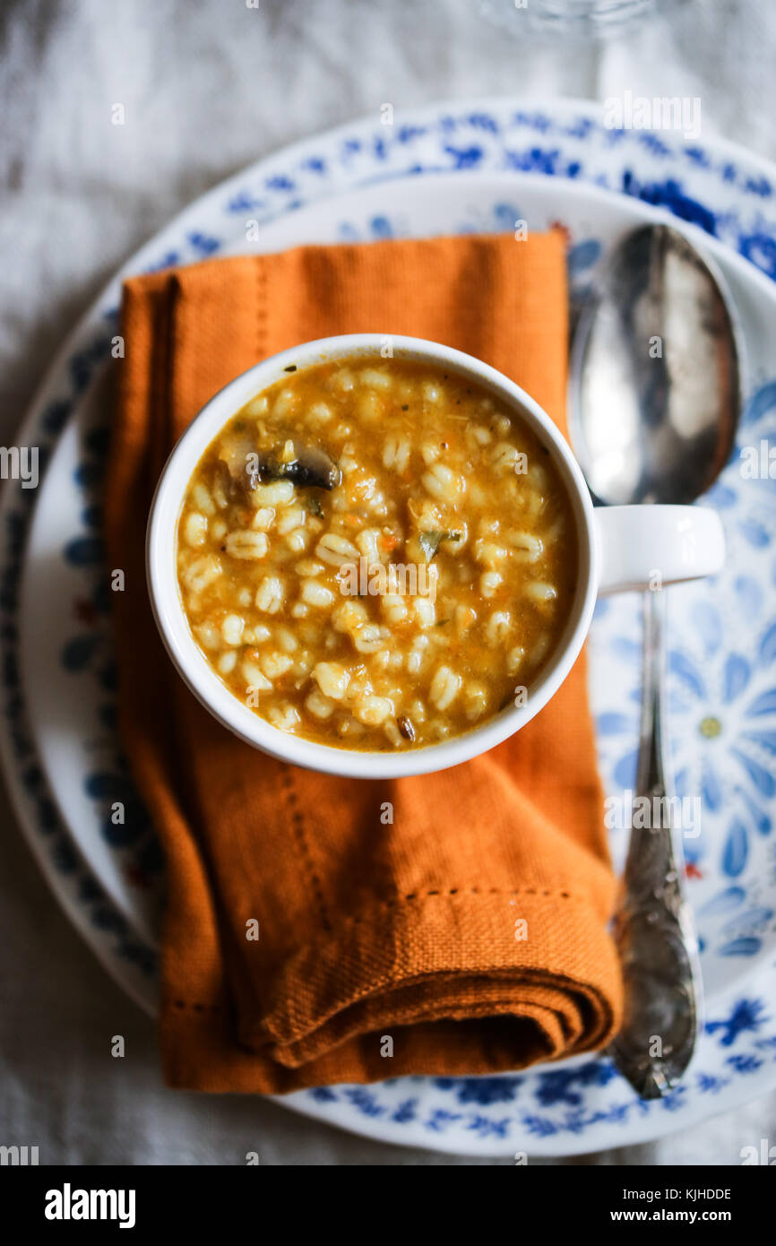 Kürbis, Pilze und Gerste Suppe in einer weißen Schüssel auf einen hölzernen Tisch. Stockfoto