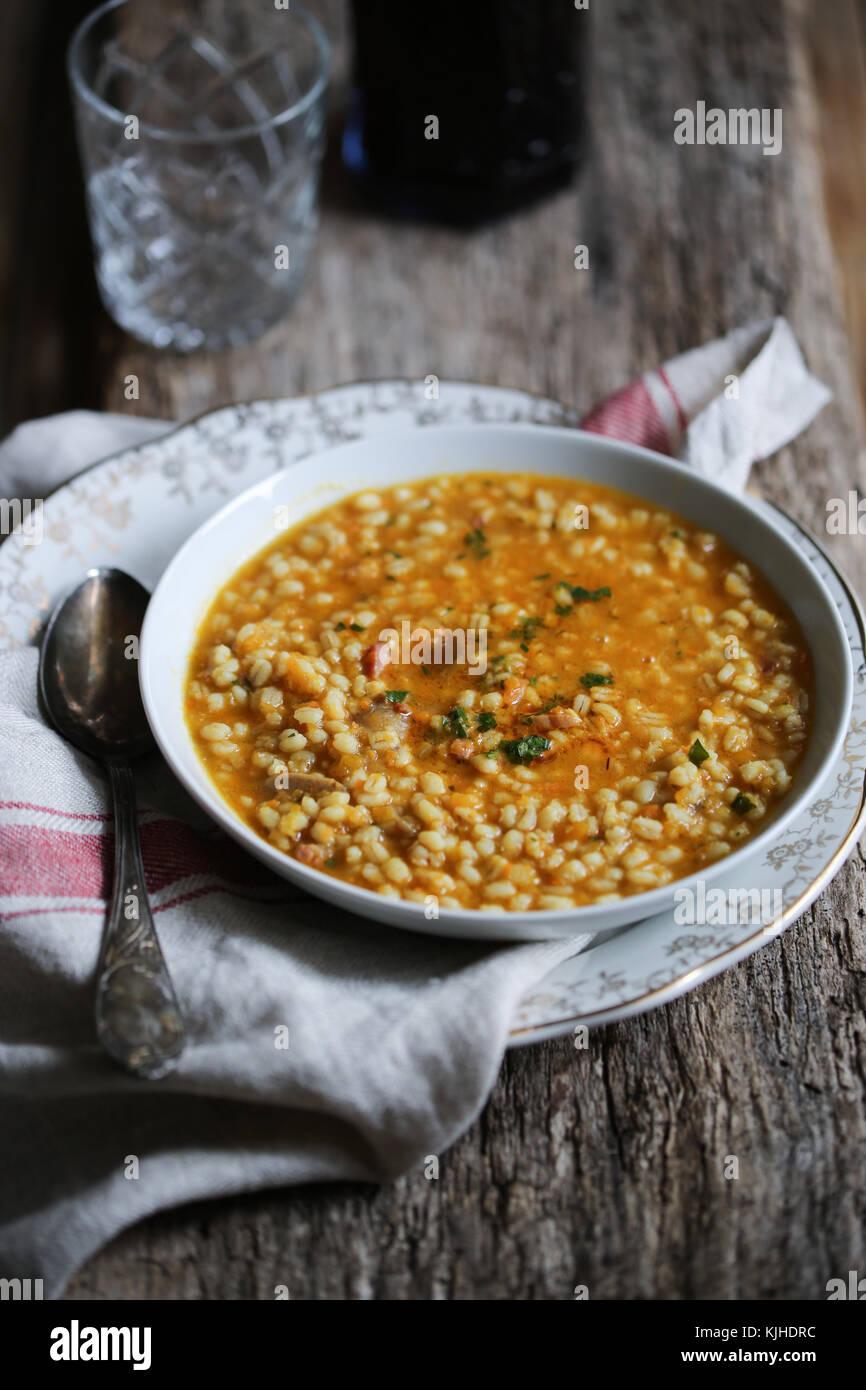 Kürbis, Pilze und Gerste Suppe in einer weißen Schüssel auf einen hölzernen Tisch. Stockbild