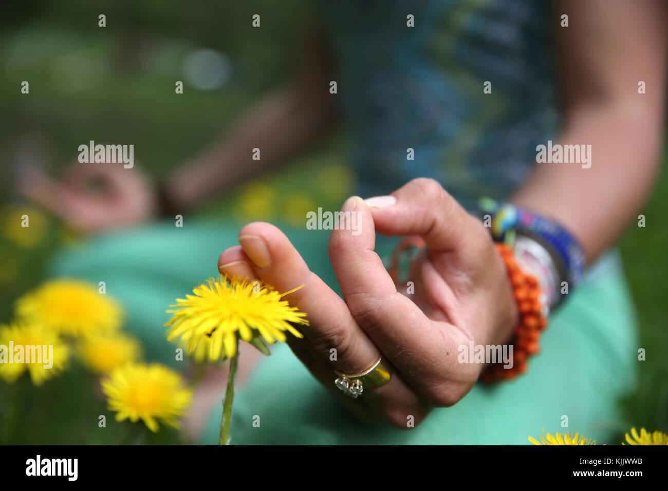 Frau Durchführung yoya außerhalb. Lotus Position und Mudra Körperhaltung. Close-up. Frankreich. Stockfoto