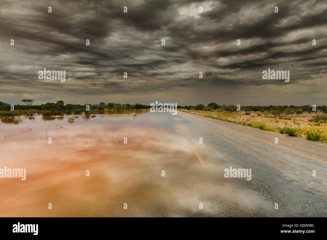 Wasser läuft über Great Northern Highway nach starkem Regen im Outback Westaustraliens. Stockbild