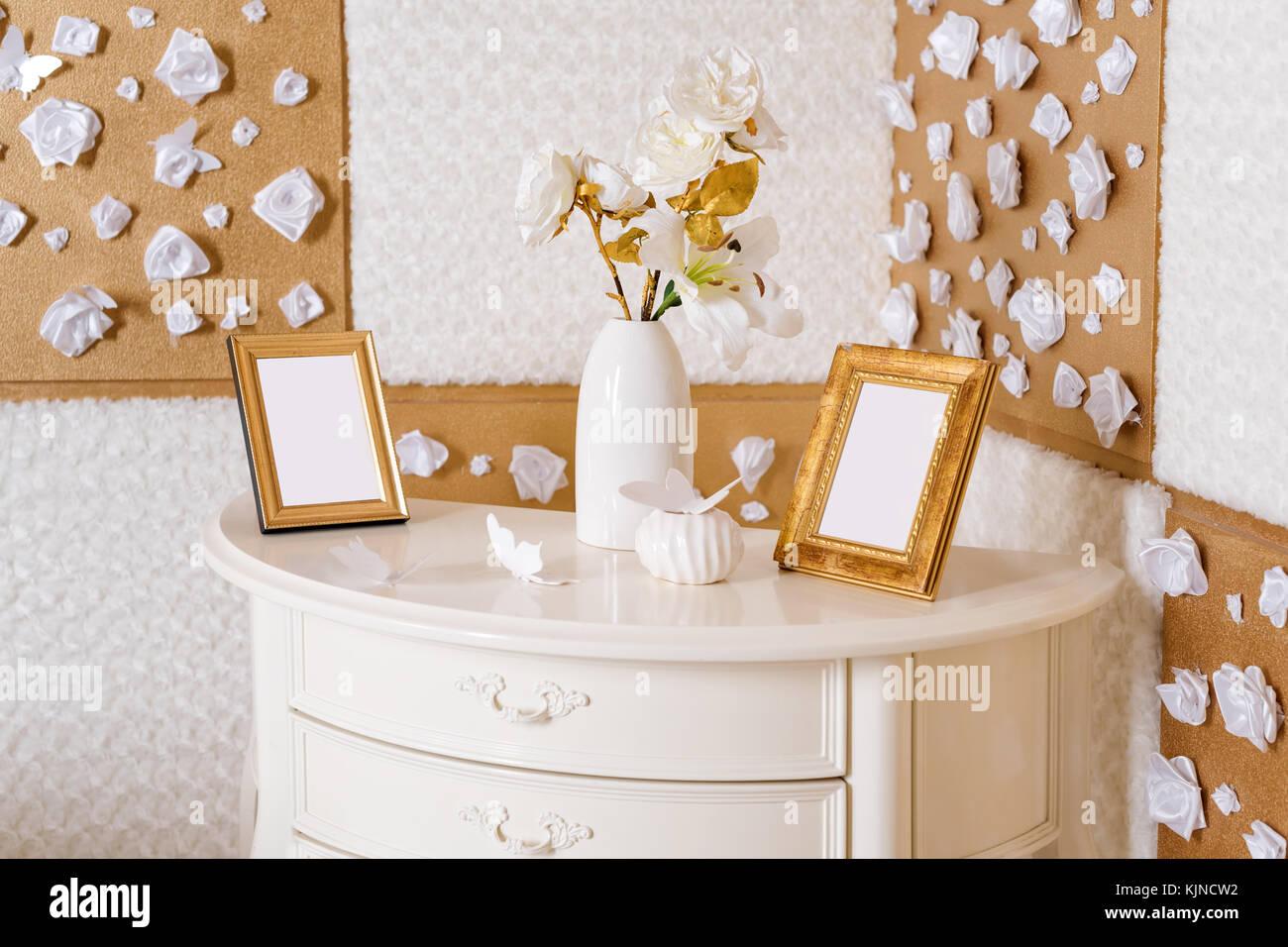 Vase mit Blumen und Bilderrahmen auf einer Tabelle in weißen und ...