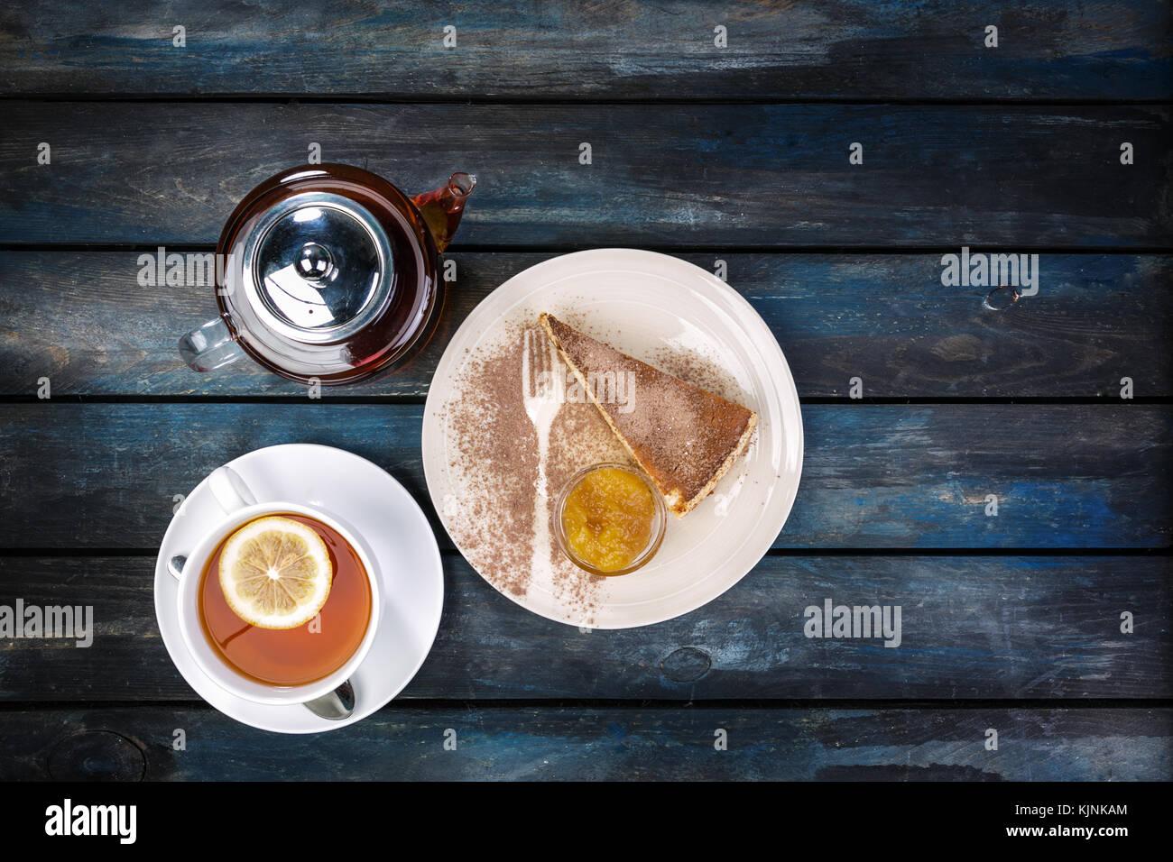 Stück Käsekuchen mit Marmelade und Tee Wasserkocher mit Zitrone auf einem farbigen Hintergrund Holz. top Stockbild