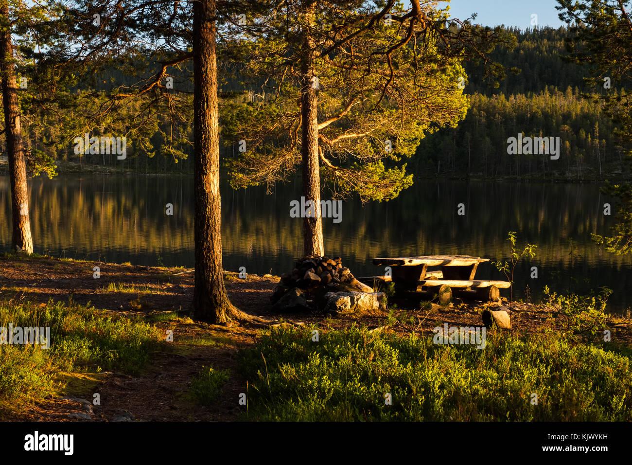 Picknicktisch am See im Abendlicht Stockbild