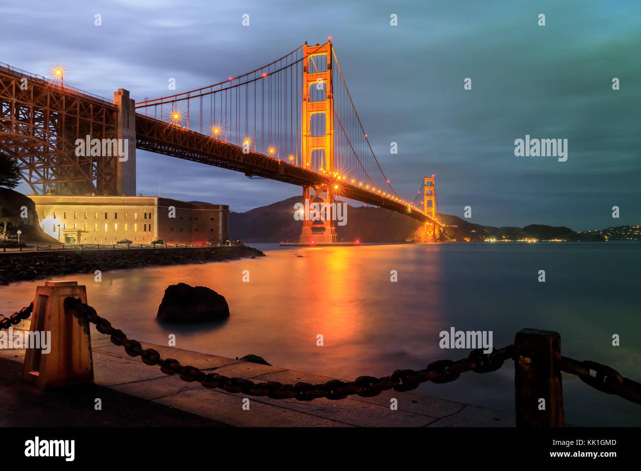 Golden Gate Bridge und Maschendrahtzaun in der Nacht. Stockbild