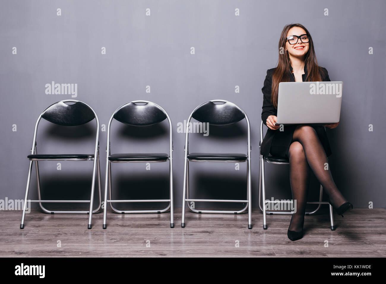 Junge lächelnde Büro Frau sitzt auf der Bodenplatte aus Holz Stuhl mit Mobile Laptop Computers bereiten Interview Stockfoto