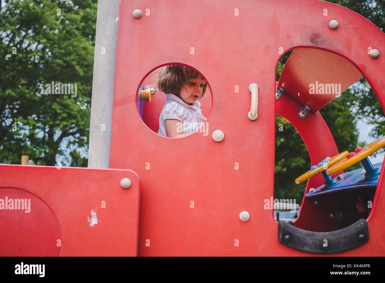 Ein kleines Mädchen klettert an Spielgeräten auf Sommer Tag Stockbild