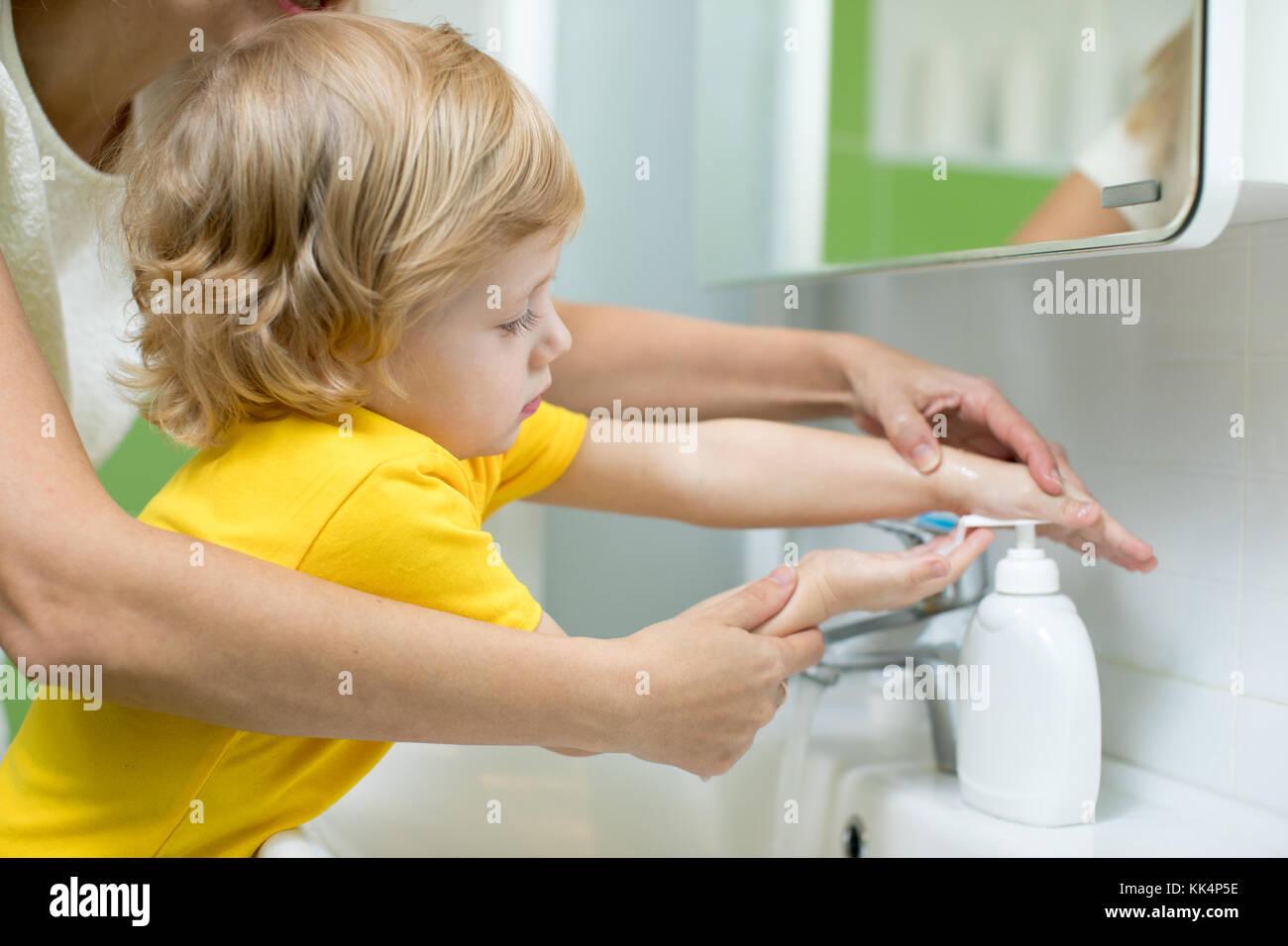Mutter und Kind Sohn waschen ihre Hände in das Badezimmer. Pflege ...