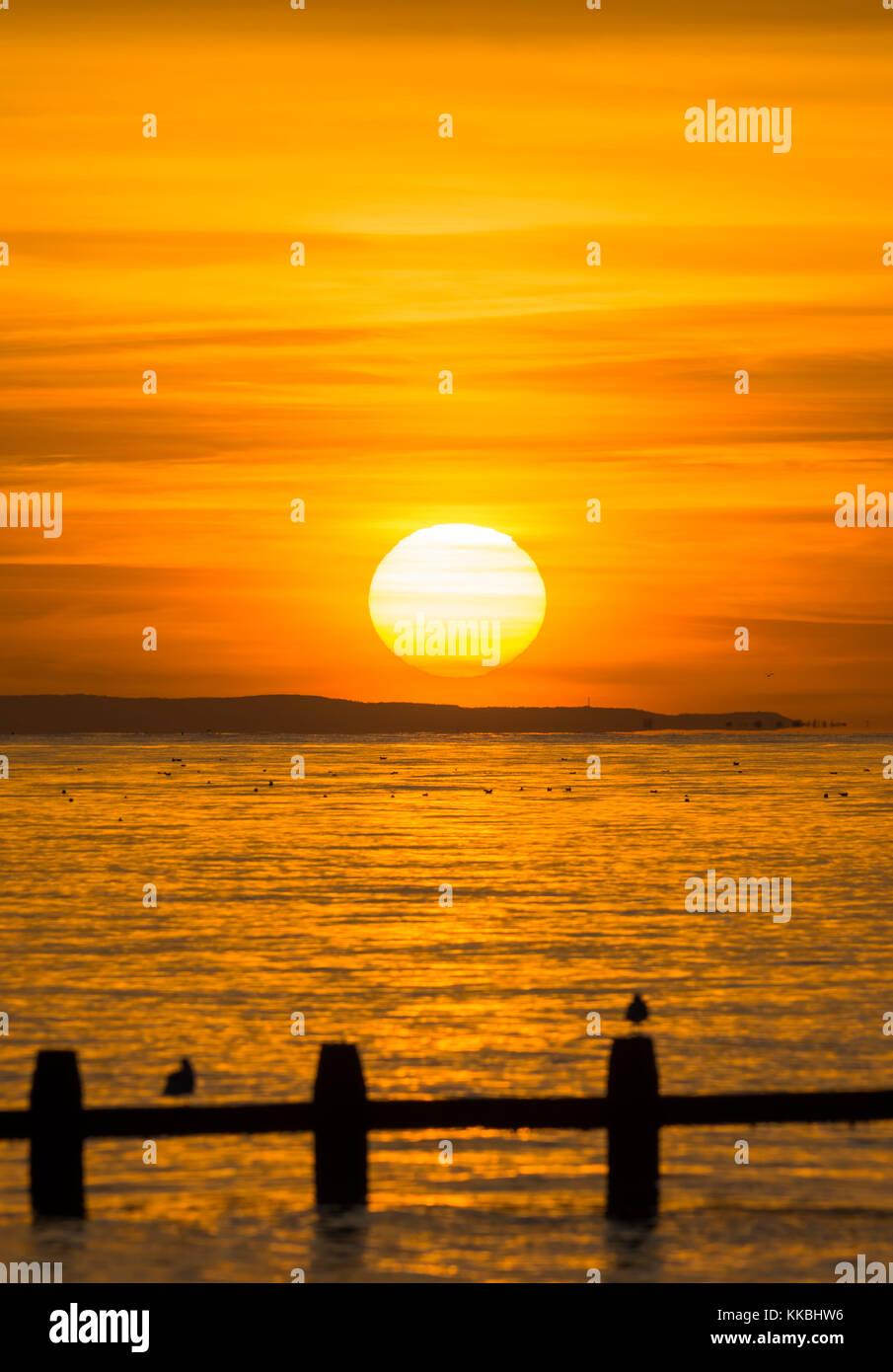 Sonnenuntergang über dem Meer knapp über dem Horizont, auf der britischen Südküste. Stockbild