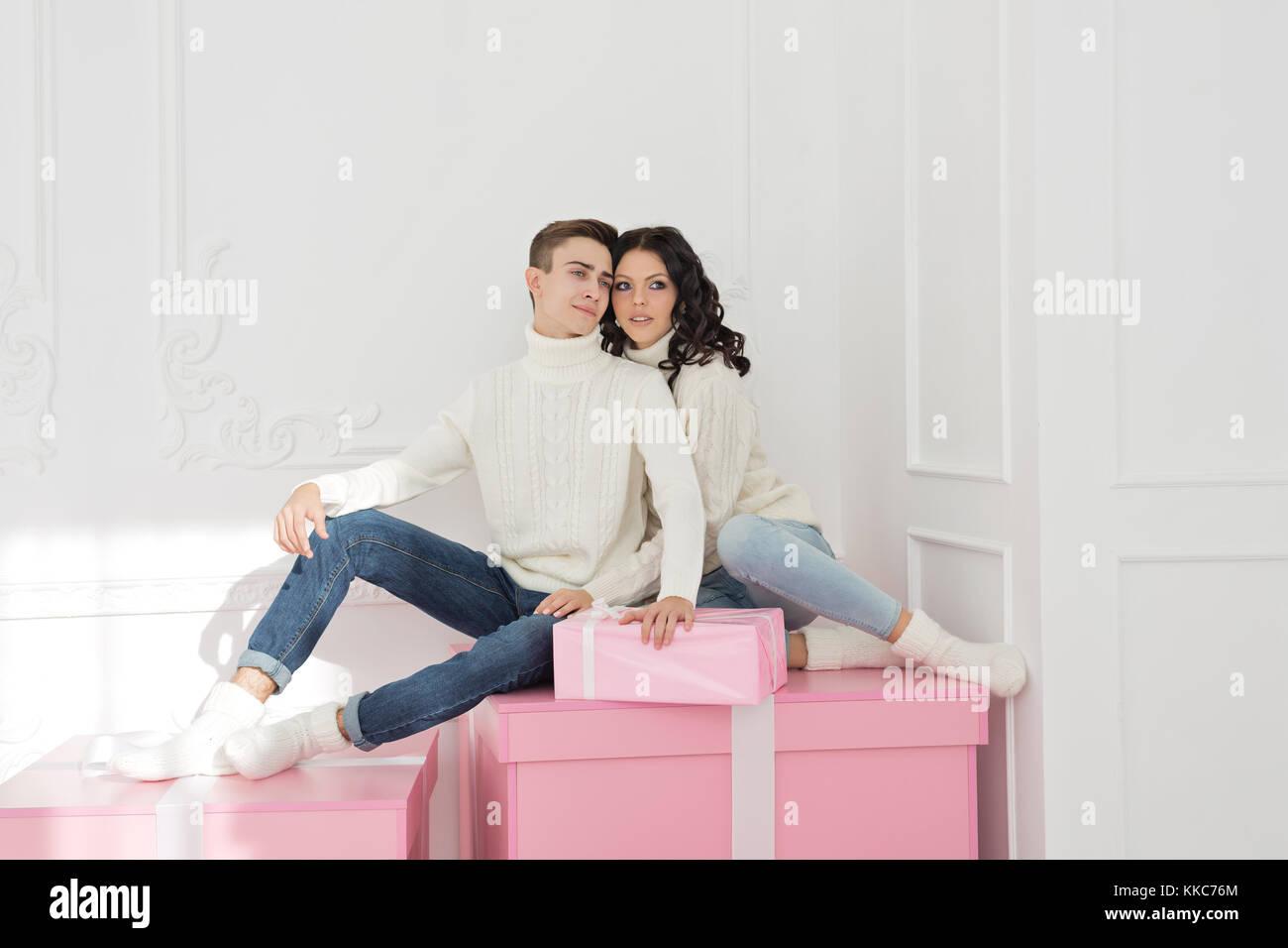 Paar Jugendliche sitzen auf Geschenke. Sie tragen die gleichen ...