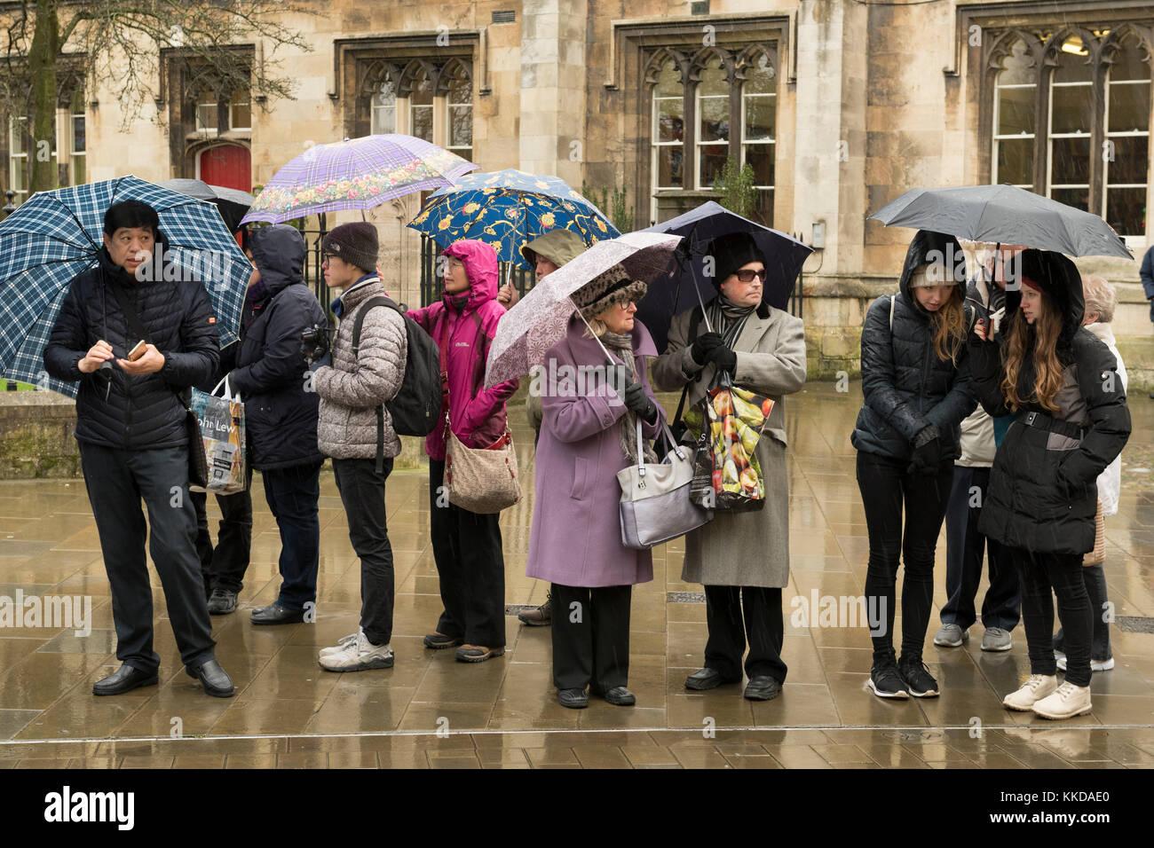 Männer & Frauen im Regen stehend, schützende unter Sonnenschirmen, warten geduldig auf Parade zu starten Stockbild