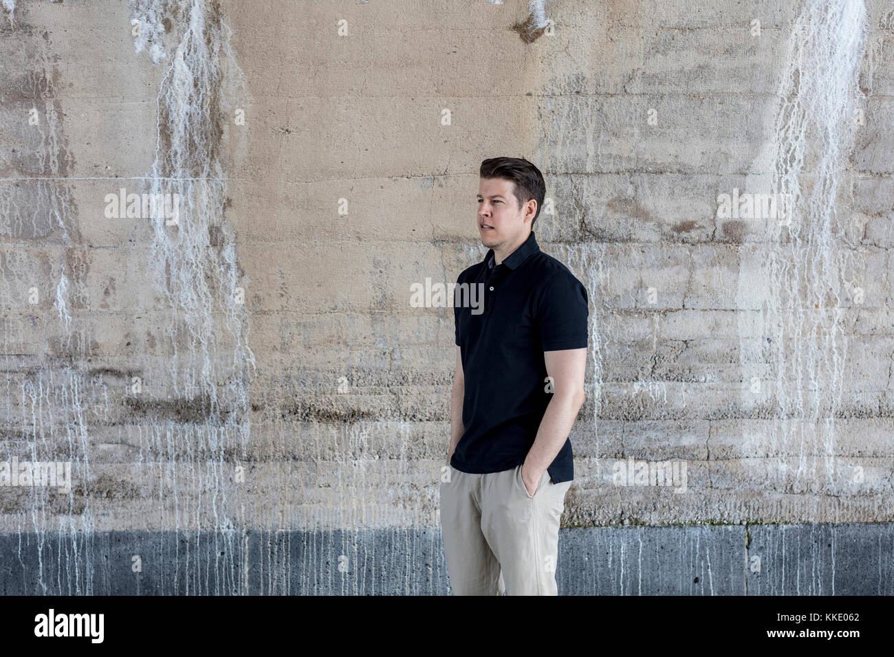 Ein salopp gekleideter Mann hinter eine beigefarbene Wand. Drei Viertel der Länge. Stockbild