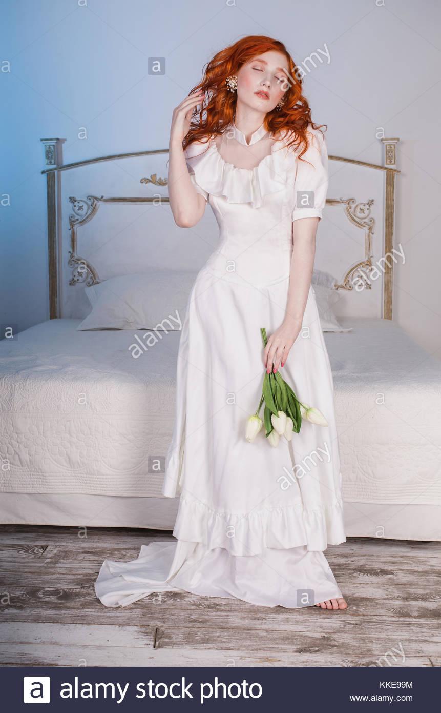 Frau mit langen roten lockigen Haar in Weiß vintage Hochzeit Kleid ...