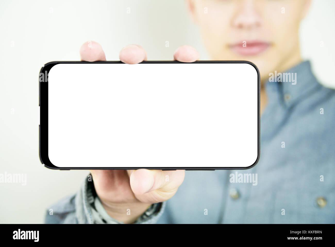 Junge Mann hält und zeigt eine leere full screen Smartphone Stockbild
