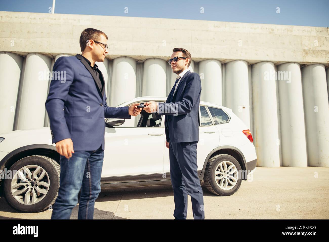 Pkw-Verkaufszahlen. eine Person verkauft Auto und gibt den Schlüssel an dem neuen Eigentümer Stockbild