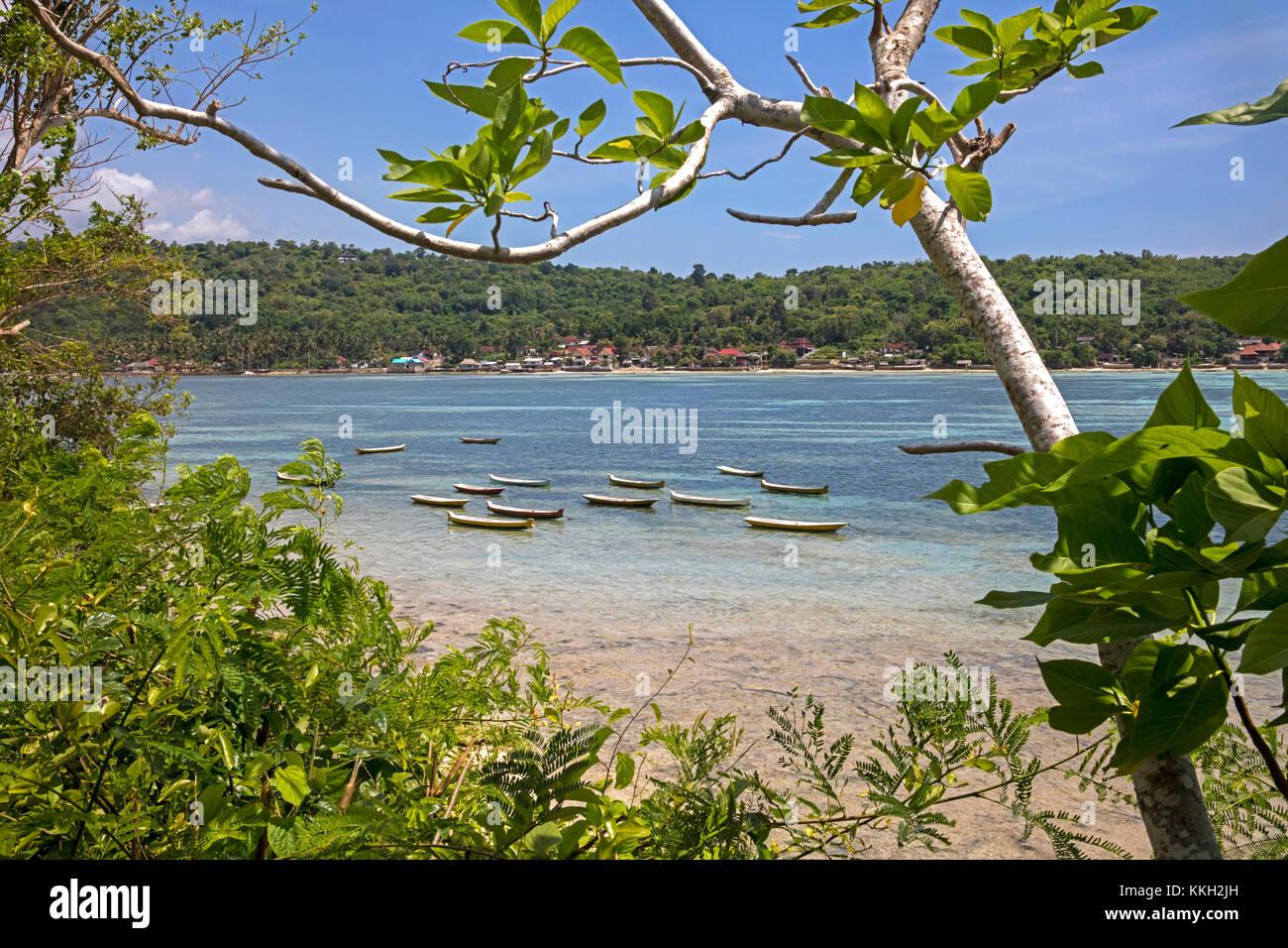 Fischerboote und Blick über Dorf an der Küste auf der Insel Nusa Ceningan von Nusa Lembongan in der Nähe von Bali Stockfoto