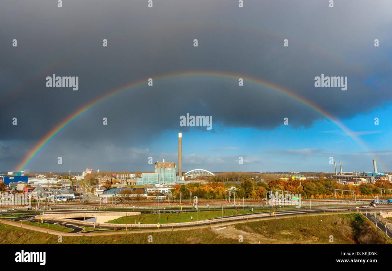 Panoramablick auf die Lageweide Business Park mit der Eneco Kraftwerk unter einem bewölkten Himmel mit Regenbogen Stockbild