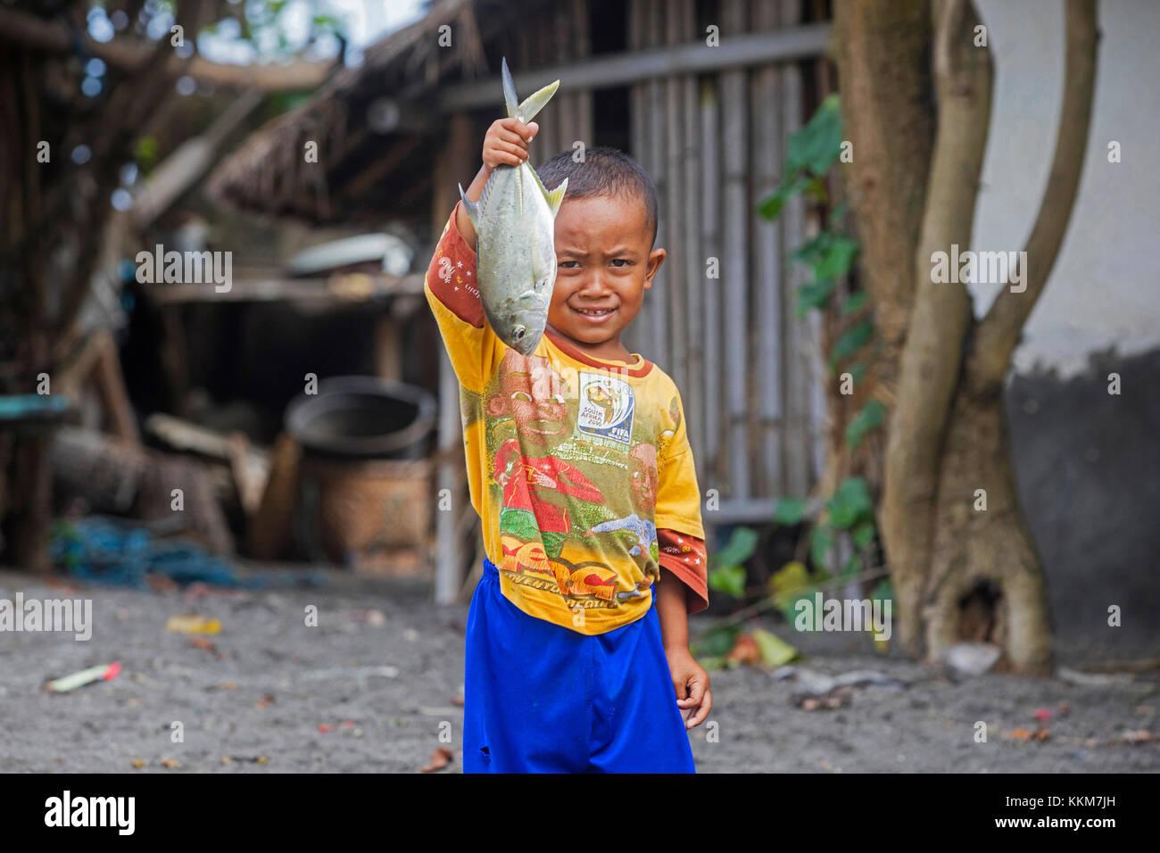 Stolz indonesischen Kind mit gefangenen Fisch in einem kleinen Fischerdorf mit Bambus Häuser auf der Insel Stockbild