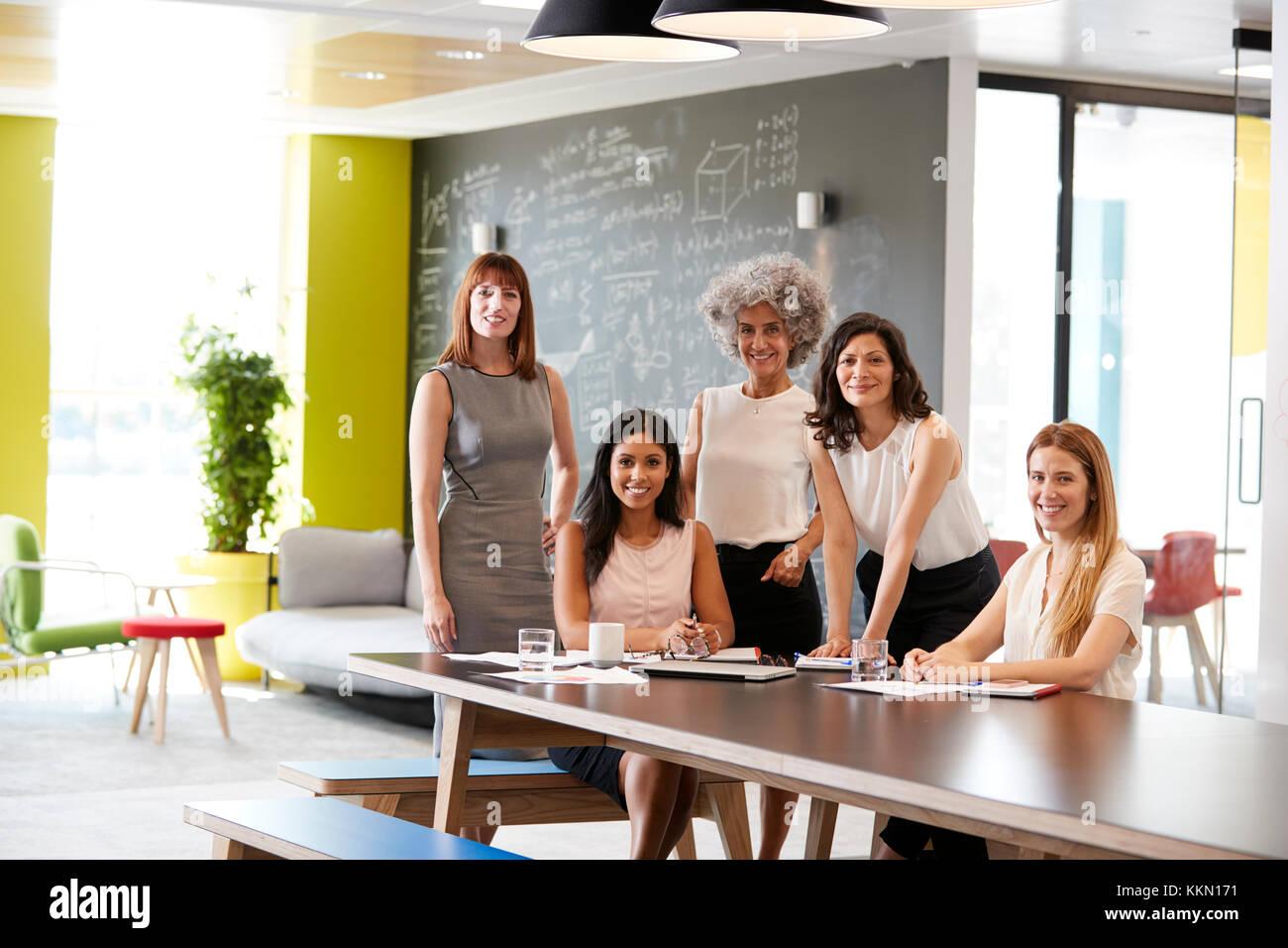 Fünf weiblichen Kollegen bei einem Arbeitstreffen lächelnd in die Kamera Stockfoto