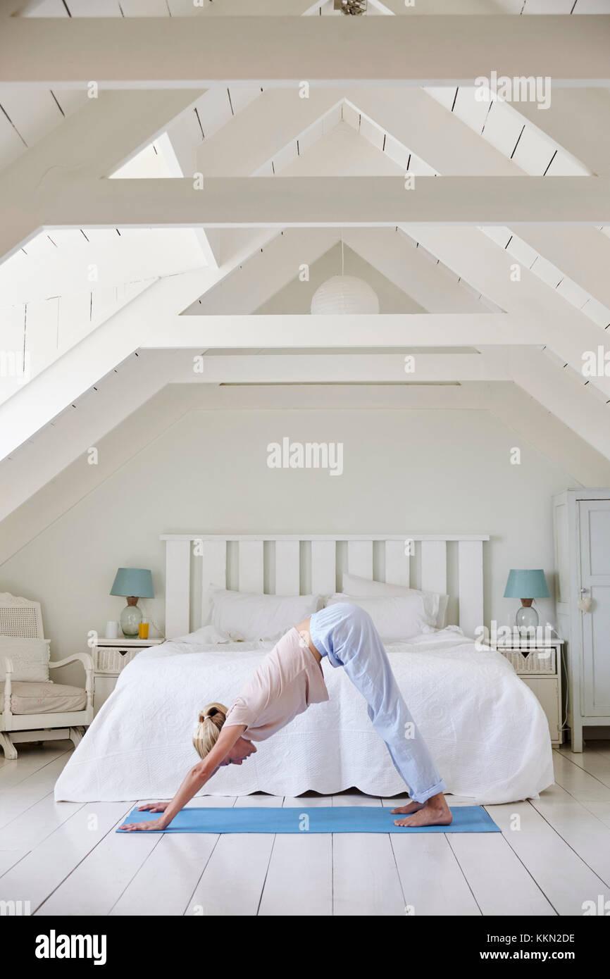 Frau zu Hause morgen beginnend mit Yoga Übungen im Schlafzimmer Stockfoto