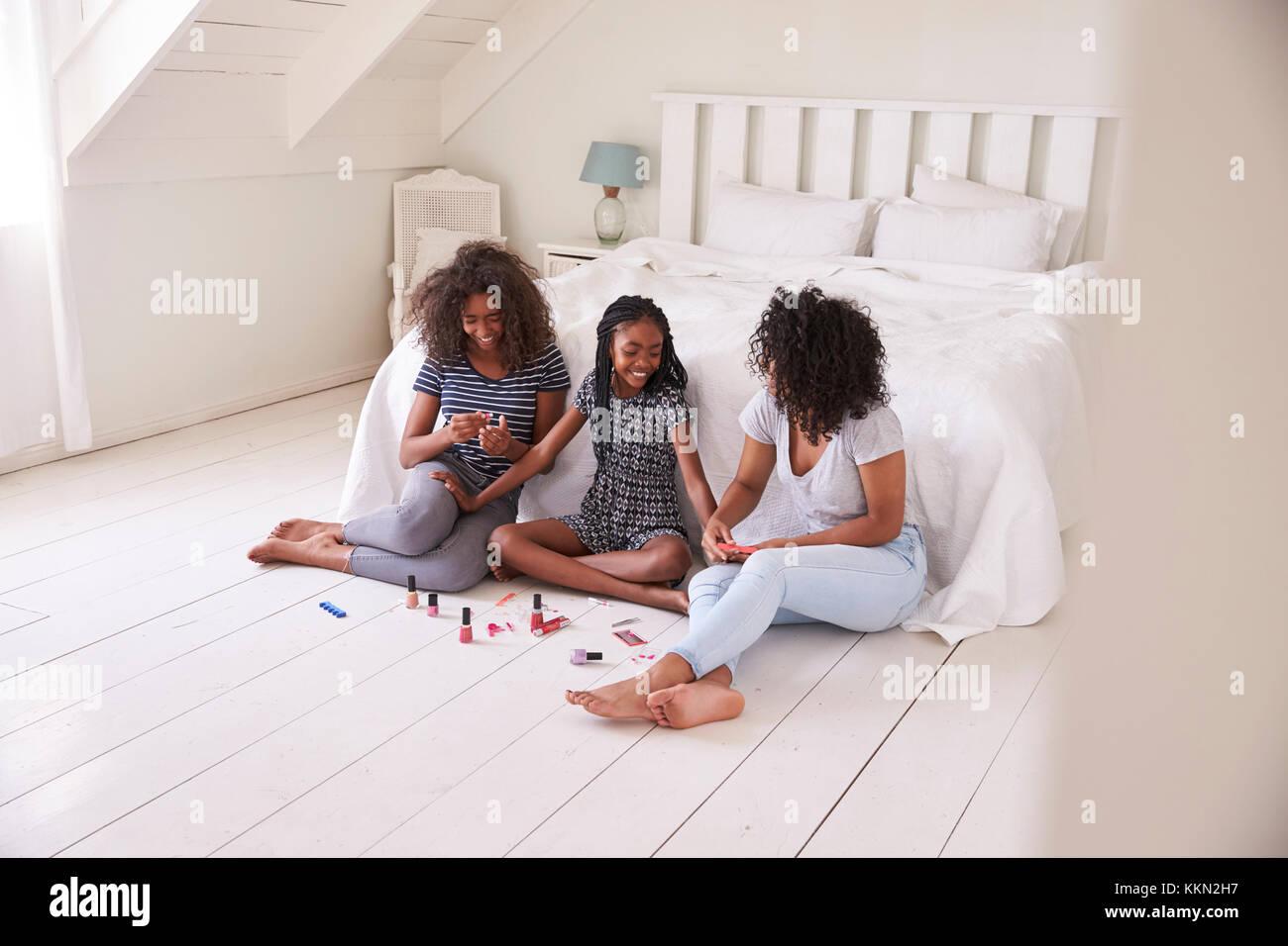 Drei Teenager Schwestern geben jedem anderen Umarbeitung im Schlafzimmer Stockbild
