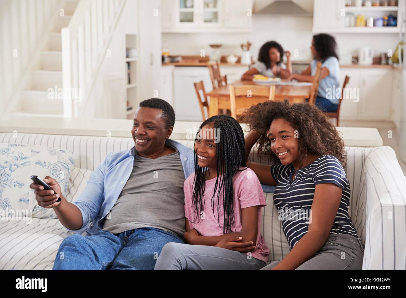 Vater sitzt auf einem Sofa Fernsehen mit Töchtern im Teenageralter Stockfoto