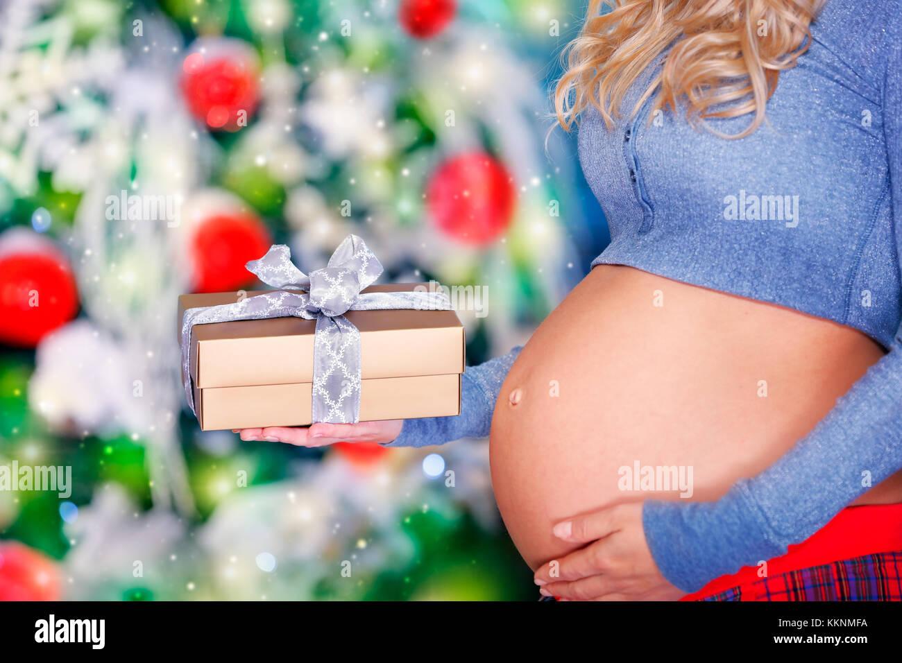 Nahaufnahme eines Bauch der schwangeren Frau mit Geschenk Box in der ...
