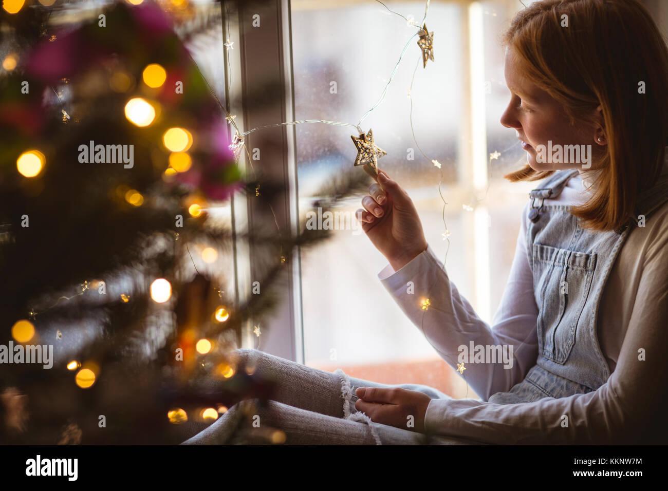 Mädchen sitzt auf der Fensterbank und Stern Stockbild