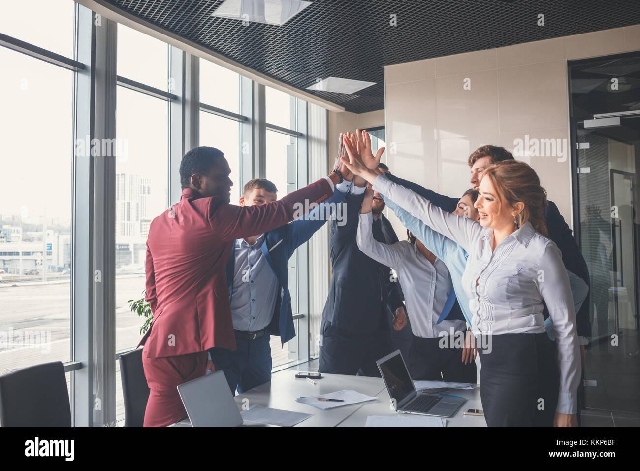 Business Team eine High Fives Geste, als sie lachen und ihren Erfolg jubeln Stockbild