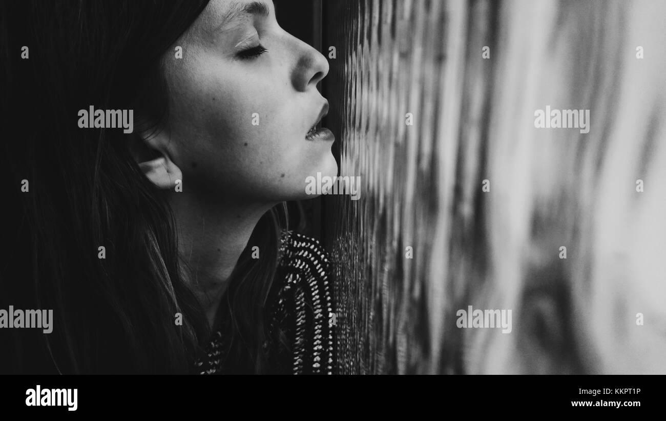 Junge Frau zu Hause vor einem Fenster Stockbild