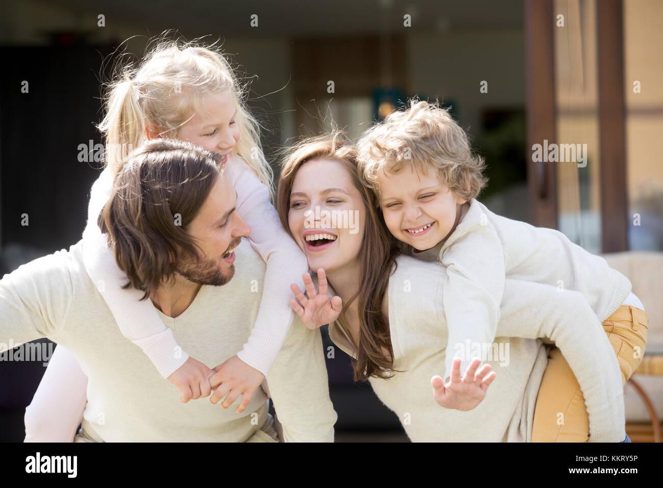 Glücklich lächelnde Eltern huckepack Sohn und Tochter, Familie leis Stockbild