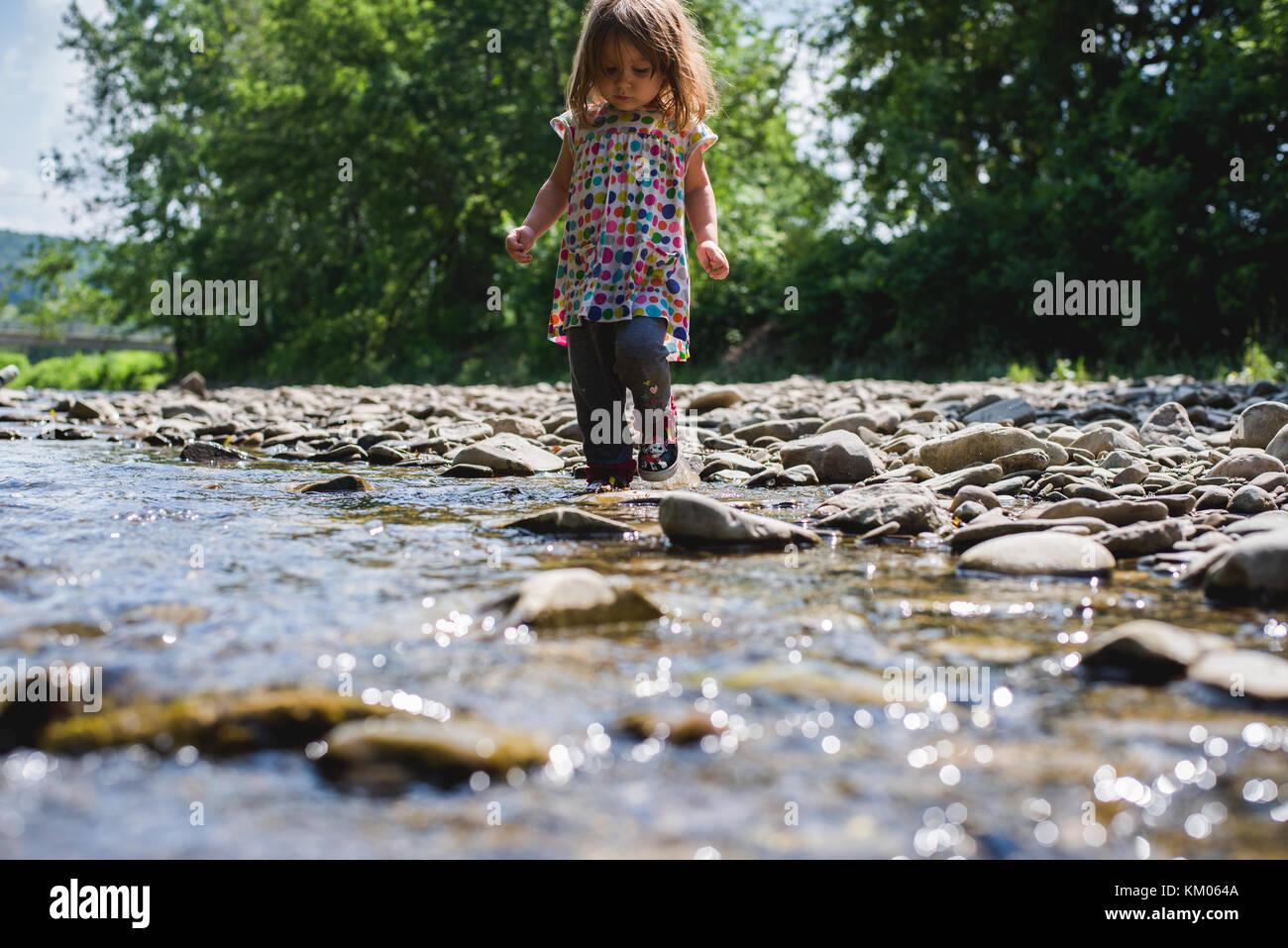 Ein kleines Mädchen steht in einem Stream auf einem sonnigen Sommertag. Stockbild
