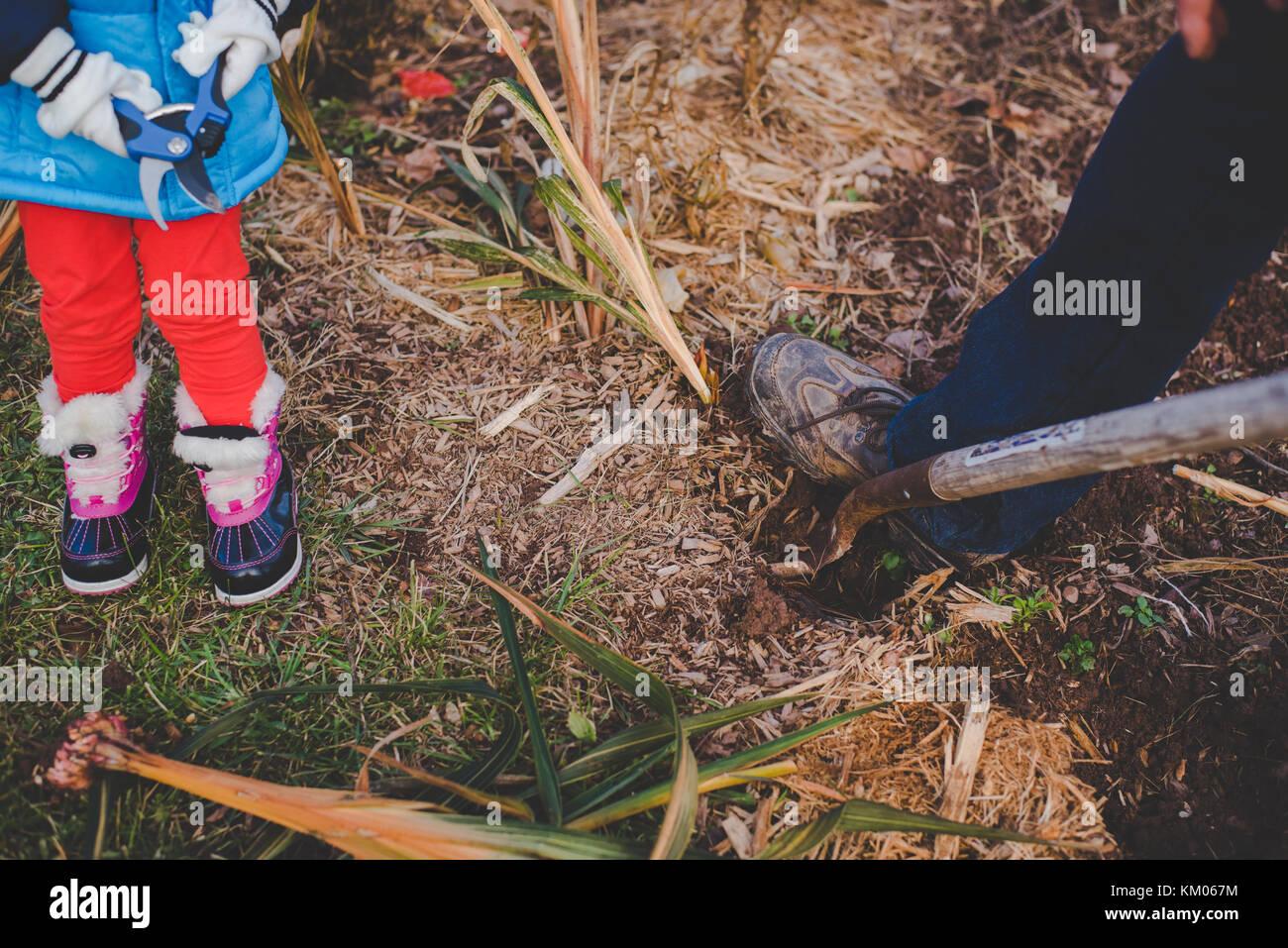 Kinder helfen ihren Großvater dig in einem Garten im Winter Stockbild