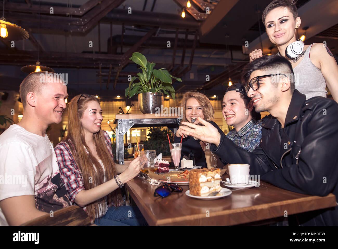 Freunde in einen Kaffee zusammen. Frauen und Männer im Cafe, reden, lachen Stockbild