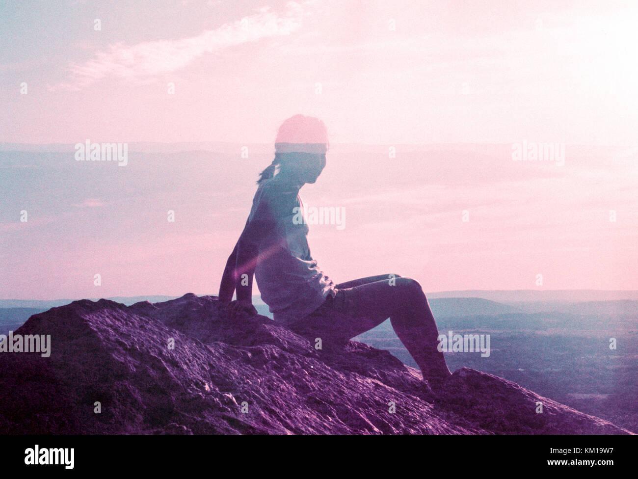 Doppelbelichtung Frau auf Felsen mit Blick auf die Landschaft bei Sonnenaufgang Stockbild