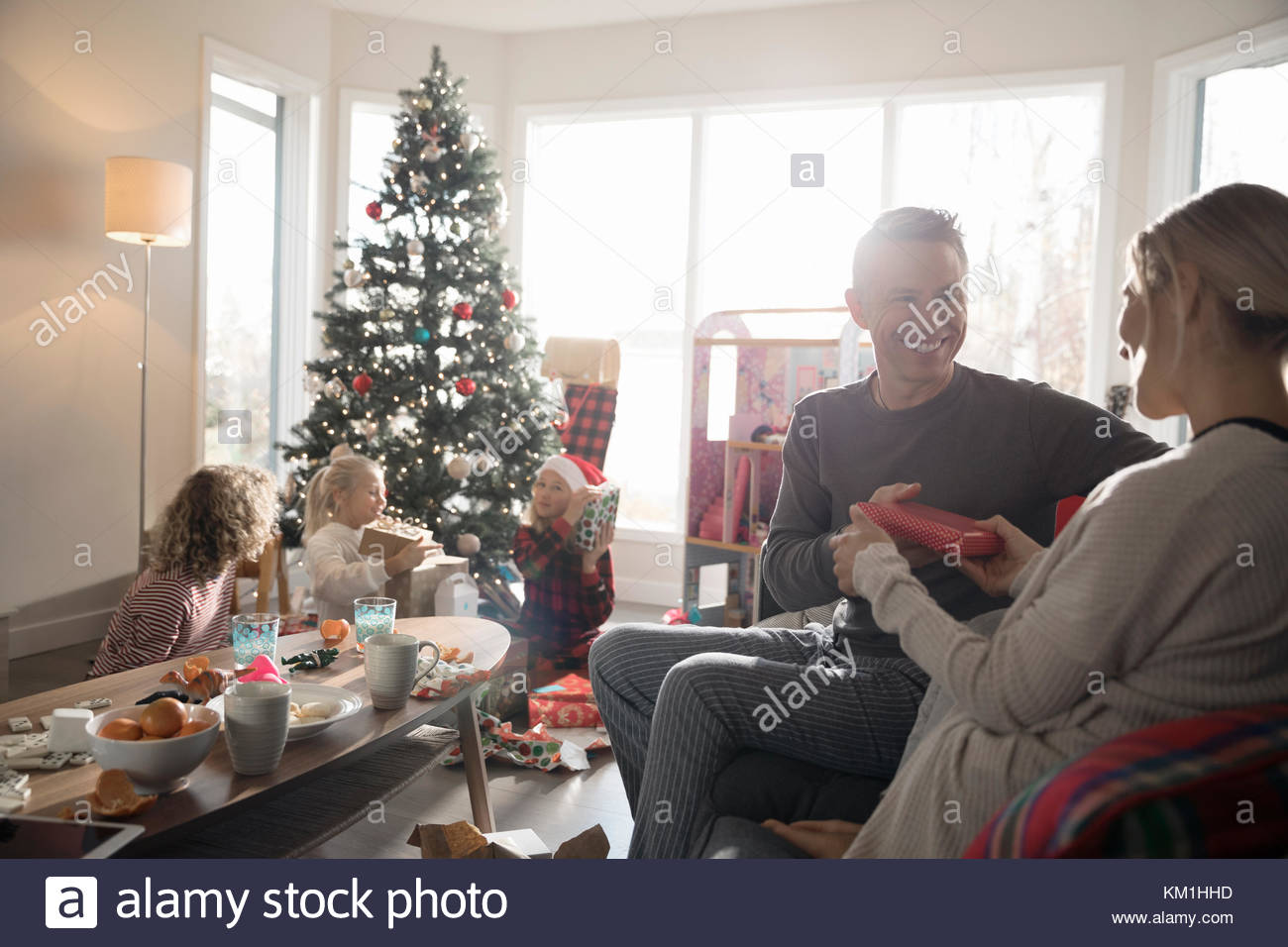 Mann, Weihnachtsgeschenk zu Frau im Wohnzimmer mit der Familie Stockbild