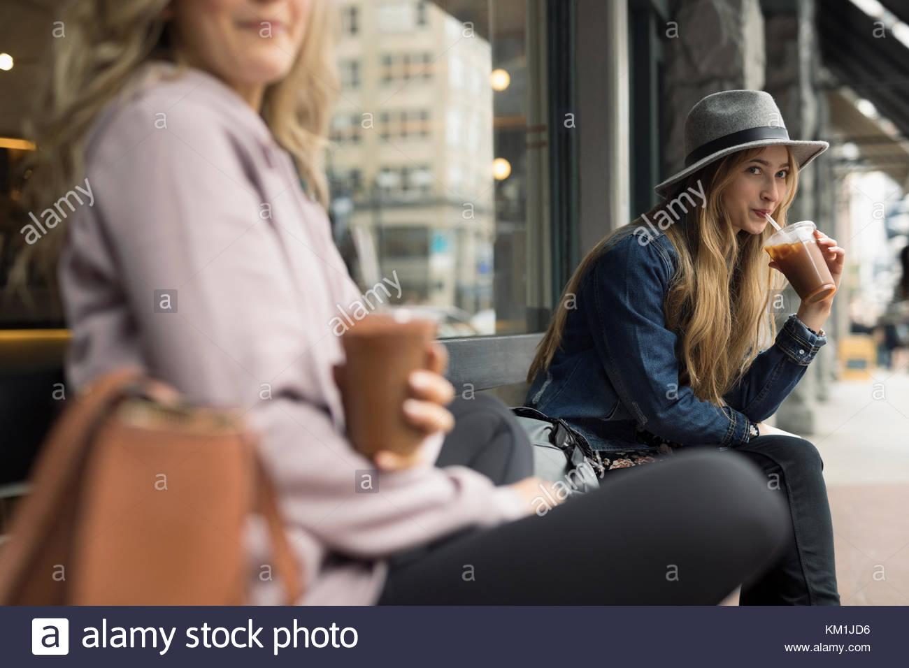 Junge Frauen, die Freunde trinken Eiskaffee auf der Werkbank im Straßencafé Stockbild