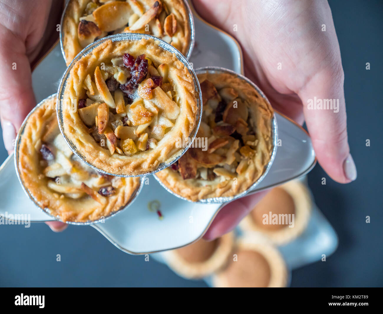 Ansicht von oben weibliche Hand Weihnachten pie Cup Cake von festlichen Stern Platte mince auf dunklem Hintergrund. Stockbild