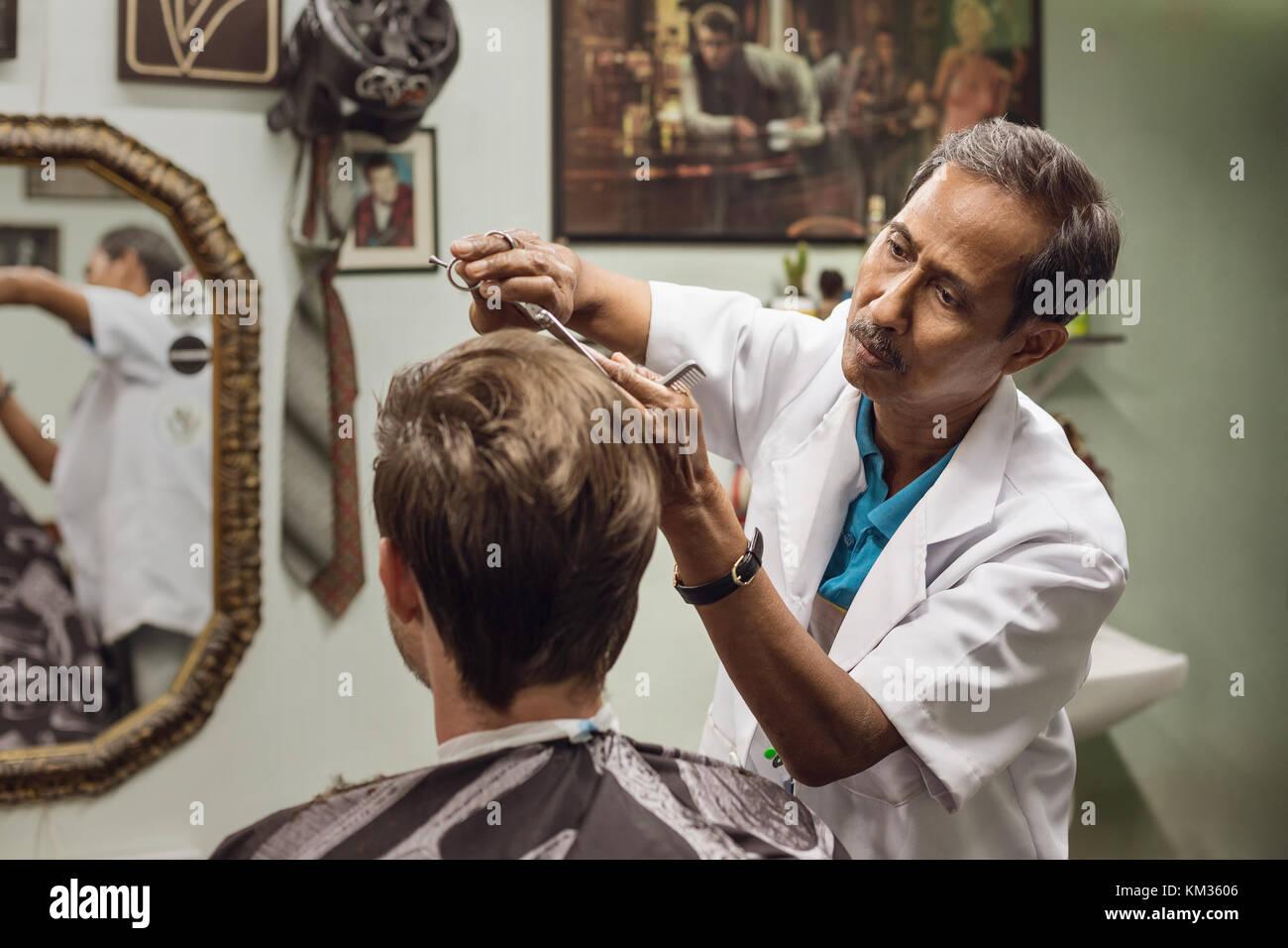 Malaiische Friseur- Konzentration bei der Arbeit Stockbild