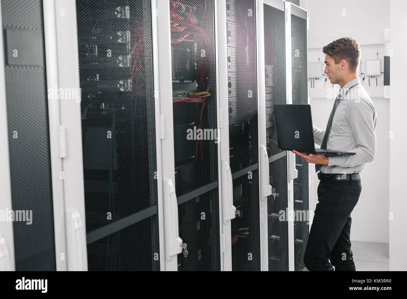 Portrait des modernen jungen Mann mit Laptop steht im Server Raum arbeiten mit supercomputer Stockbild