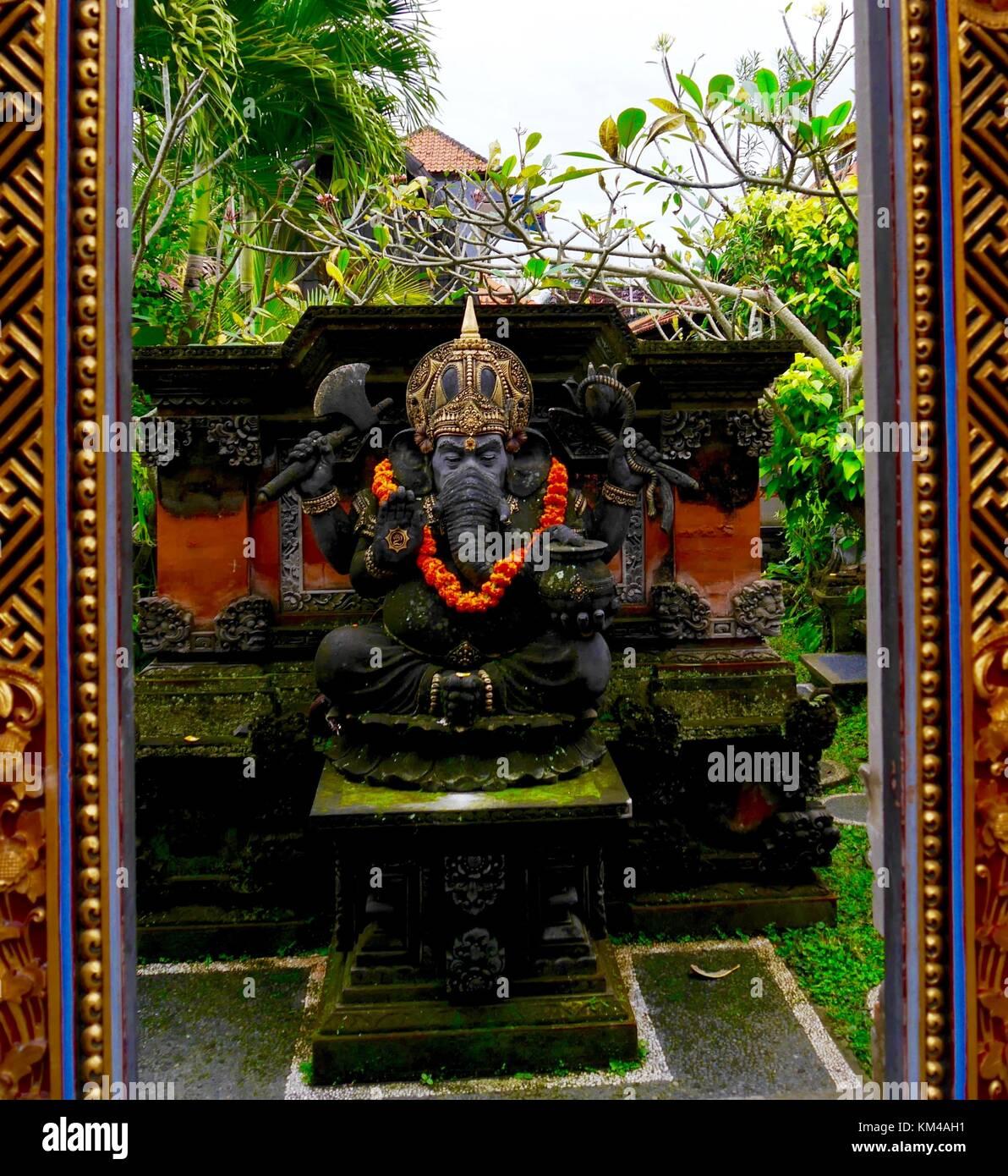 Vertikaler statue Der elefantenköpfige Ganesha Hindu Gott (Ganesh) mit Ringelblume Girlande im grünen Haus Garten, Stockfoto